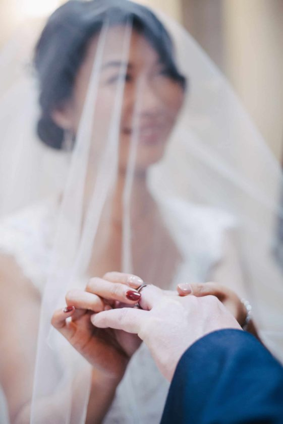 bride putting a ring on the groom
